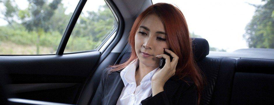 Woman speaking on cell phone in back seat of a town car
